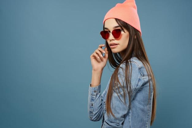 Donna in cappello rosa occhiali da sole giacca di jeans hipster sfondo blu