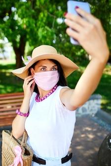 La donna in maschera medica rosa nel parco prende selfie con il cellulare, la donna con protezione respiratoria è all'aperto mentre parla e ha chat video tramite webcam sullo smartphone