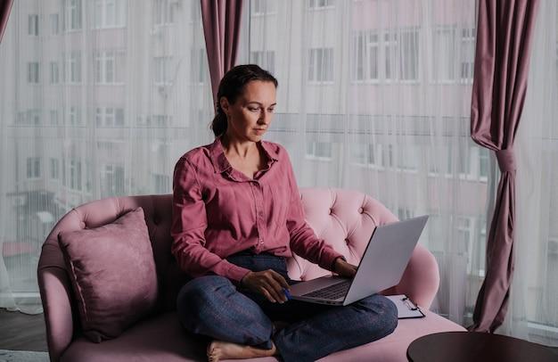 Una donna con una maglietta rosa è seduta sul divano con un laptop e lavora