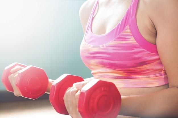 Donna in reggiseno sportivo in rosa holding dumbbells rossi. concetto di allenamento