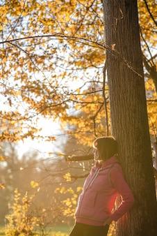Donna in maglione rosa che si appoggia contro l'albero all'aperto nella stagione autunnale con foglie gialle.