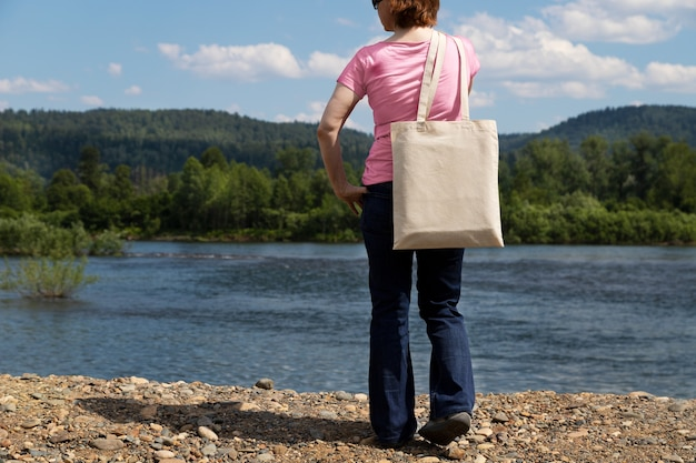 Donna in maglietta rosa che trasporta mockup di borsa della spesa riutilizzabile vuota.