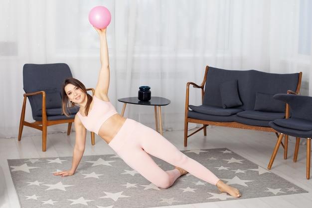 Una donna in tuta rosa si trova sull'asse laterale e tiene in mano una palla rosa per pilates