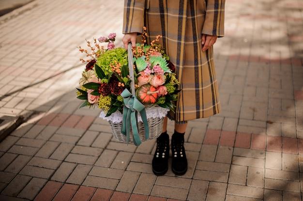 Donna in cappotto a quadri che tiene un grande cestino di vimini di bella composizione nel fiore di autunno