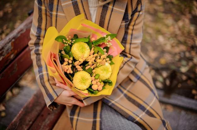 Donna in cappotto scozzese seduto sulla panchina con un mazzo di fiori gialli