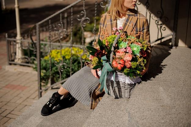 Donna in cappotto plaid seduto su scale di cemento con un cesto di vimini di fiori