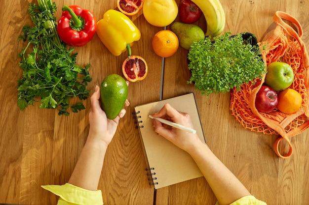 Donna che pianifica, scrive pasti settimanali su una nota di pianificazione dei pasti o su un piano dietetico