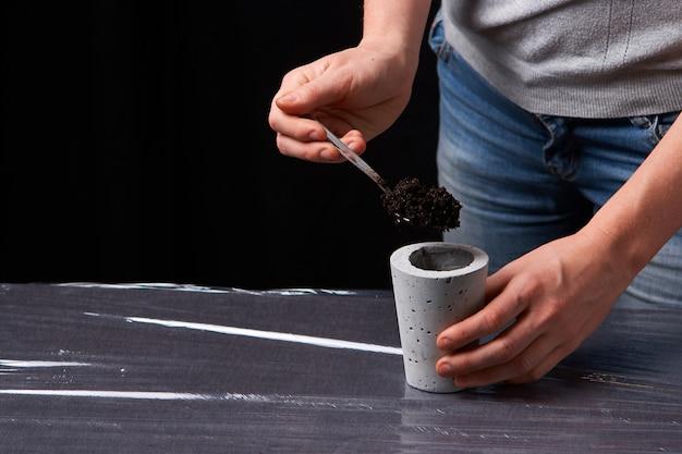 Donna che pianta succulente in vaso di cemento.