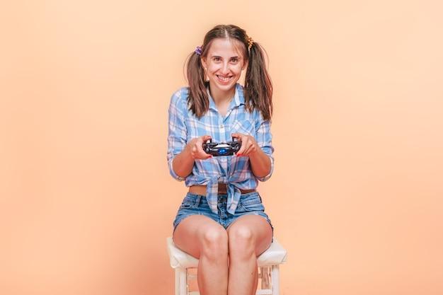 Donna che gioca giochi per computer con un joystick su una parete gialla