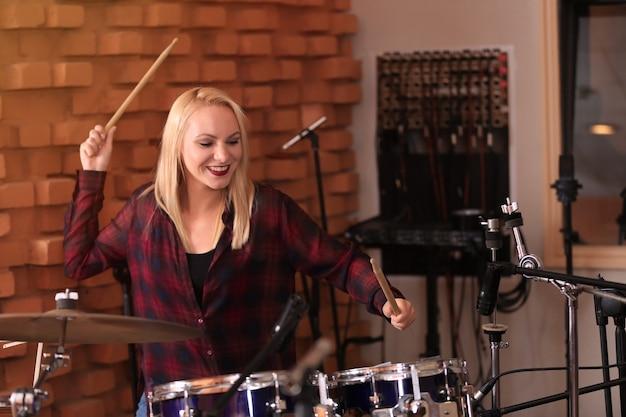 Donna che suona la batteria in uno studio di registrazione