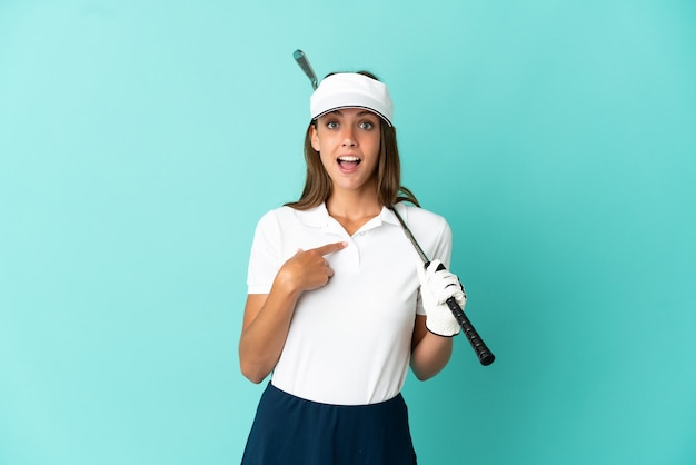 Donna che gioca a golf su sfondo blu isolato con espressione facciale di sorpresa
