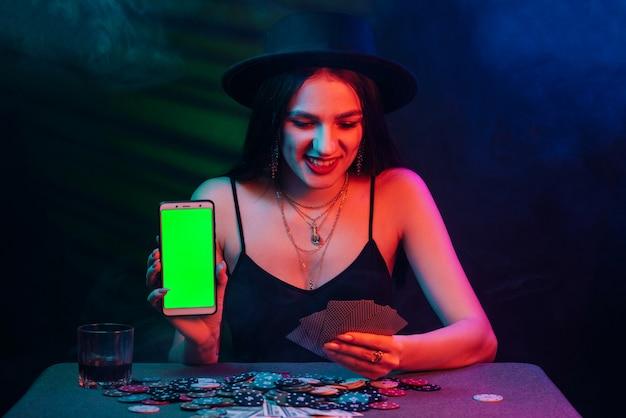 Donna che gioca a poker e tiene in mano uno smartphone con schermo verde su sfondo nero