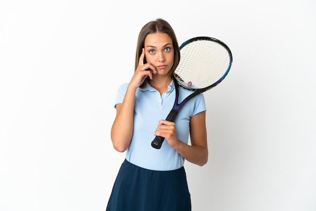 La donna che gioca a tennis ha isolato la parete bianca che pensa un'idea