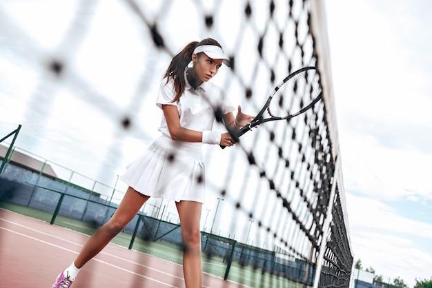 Donna che gioca a tennis e aspetta il servizio