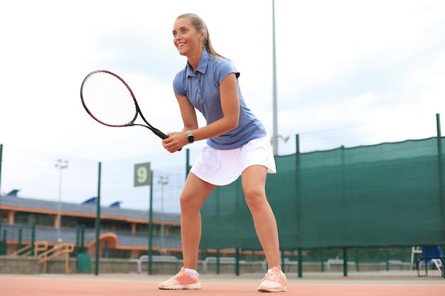 Donna che gioca a tennis e aspetta il servizio.