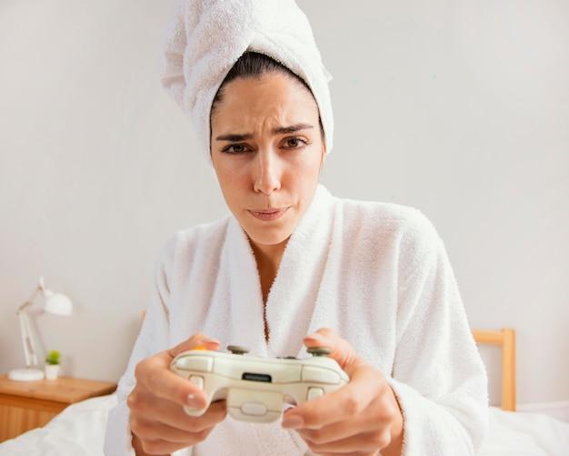 Donna che gioca ai videogiochi a casa dopo il bagno