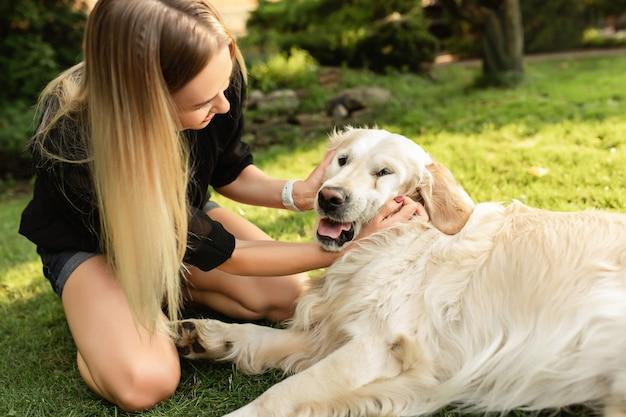 Donna che gioca con il cane labrador nel parco verde