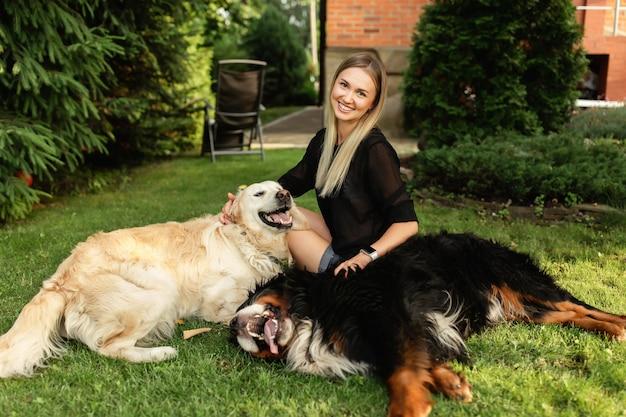 Donna che gioca con il cane labrador e sennenhund all'aperto nel verde del parco. amicizia di persone e animali