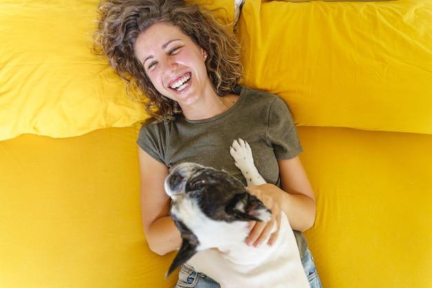 Donna che gioca con il cane su sfondo giallo. vista dall'alto del cane a letto con una donna felice che guarda in alto
