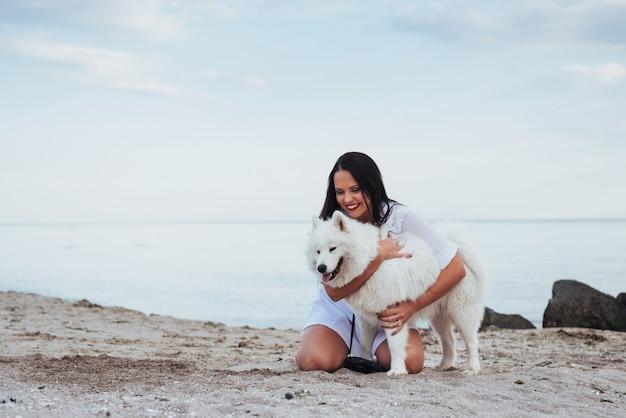 Donna che gioca con il suo cane sulla spiaggia