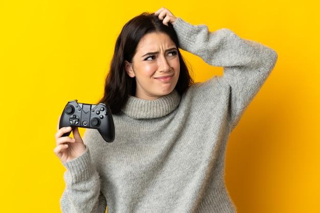 Donna che gioca con un controller per videogiochiisolrted su sfondo giallo con dubbi e con espressione del viso confusa