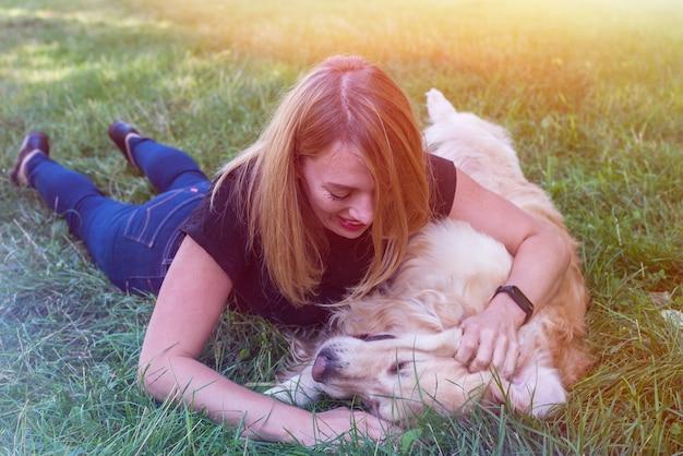 La donna gioca con il suo cane da riporto all'aperto.