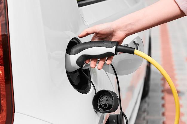 Donna che collega l'auto elettrica alla stazione di ricarica elettrica all'aperto con edificio. concetto di auto ecologico.