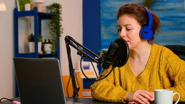 Podcast donna che registra podcast audio su computer portatile con cuffie e microscopio in studio domestico