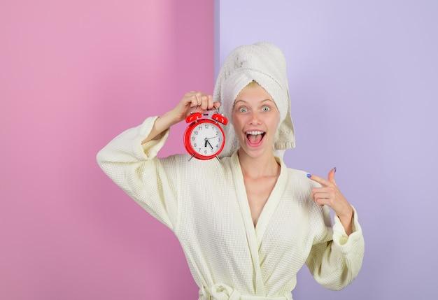 Donna che indica sulla sveglia casalinga con la sveglia che sveglia ragazza felice con la sveglia persone