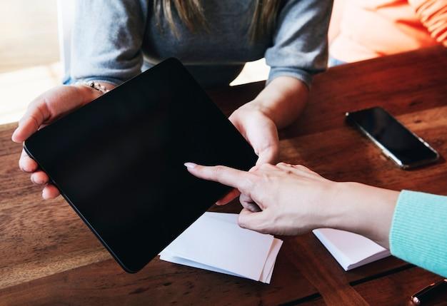 Donna che indica sullo schermo di una tavoletta digitale