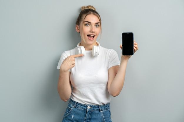 Donna che punta il dito contro lo schermo mobile vuoto
