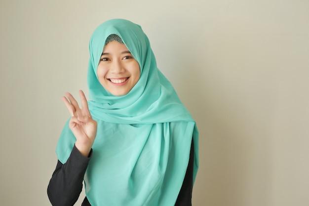 Donna che indica il numero 3 in su, modella donna musulmana asiatica
