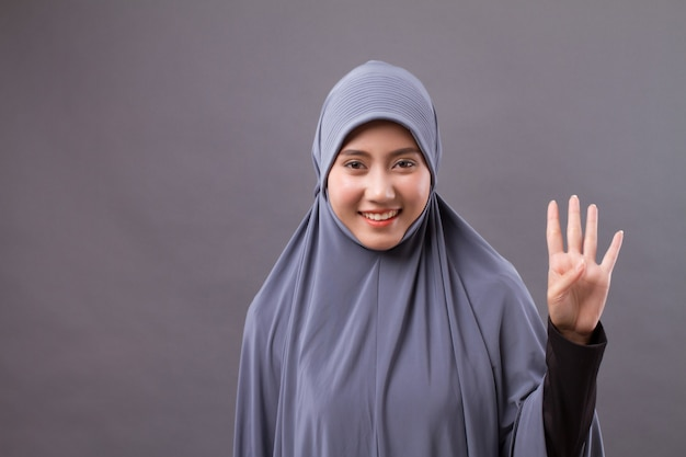 Donna che indica il numero 4 in alto, modello di donna musulmana asiatica