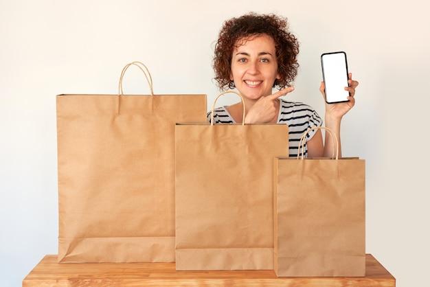 Una donna indica il cellulare accanto ad alcune borse della spesa