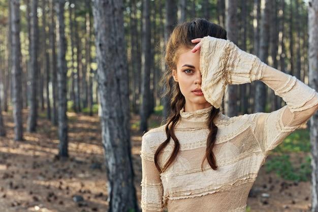 Ritratto di donna in mano foresta vicino conifere vestito aria fresca viso. foto di alta qualità