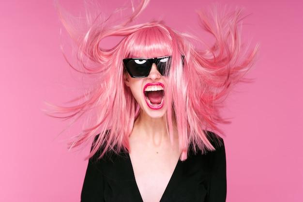 Ritratto di donna capelli rosa, parete rosa, occhiali e accessori
