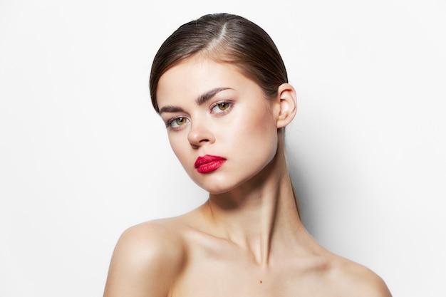 Ritratto di donna labbra rosse scoperte spalle pelle chiara trattamenti termali trucco luminoso sfondo chiaro