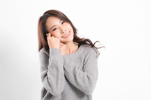 Ritratto di donna con una pelle perfetta e indossa un maglione grigio isolato su bianco.