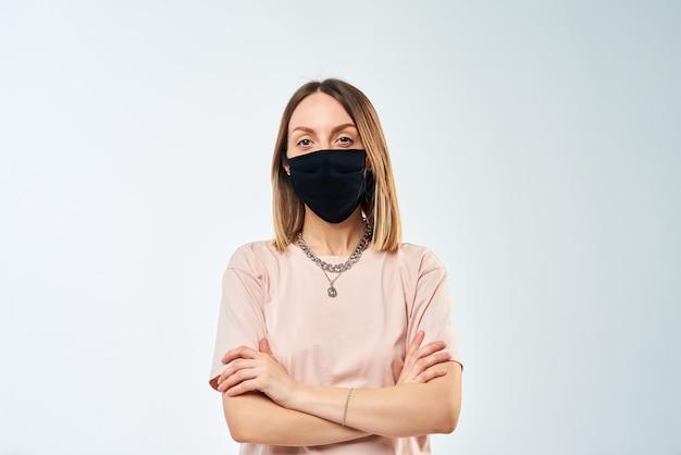 Ritratto di donna con maschera protettiva sul viso sul muro bianco