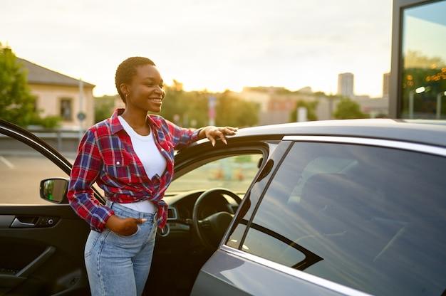 La donna posa in macchina pulita, stazione di lavaggio auto a mano
