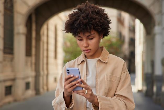 La donna posa in un ambiente urbano con lo smartphone digitale naviga in internet indossa una giacca beige sta fuori ha una vacanza di viaggio da sola
