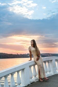 Donna che propone in vestito prima del lago nella città moderna