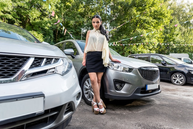 Donna in posa vicino a nuove auto sul parcheggio