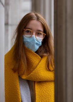 Donna in posa all'aperto con mascherina medica