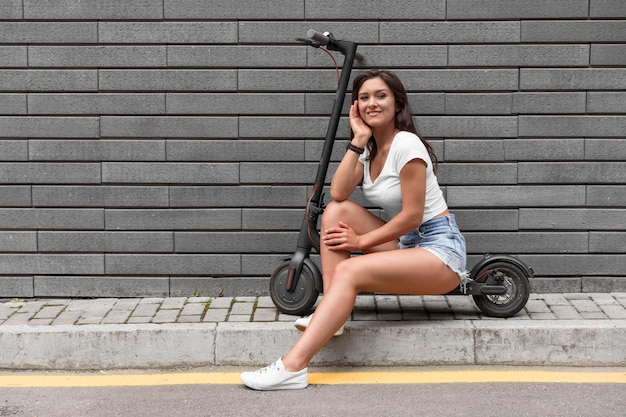 Donna in posa mentre è seduto su uno scooter elettrico