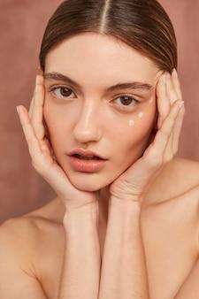 Donna in posa con crema per il viso da vicino
