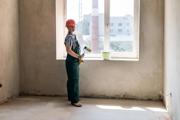 Donna in posa con il rullo per la pittura e il secchio di tinta
