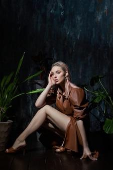 Donna che posa con le foglie tropicali