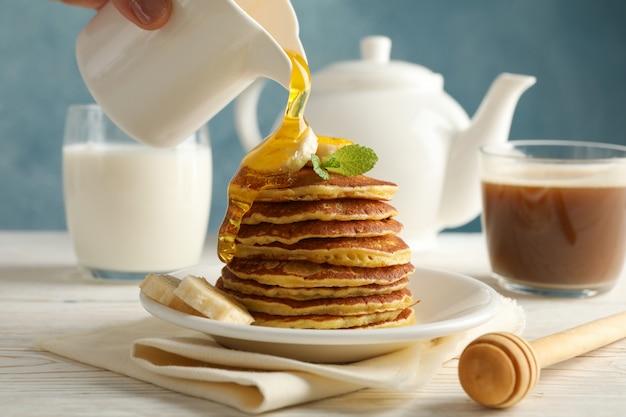 La donna versa il miele sui pancake. colazione dolce