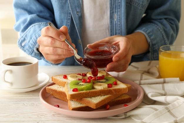 La donna versa la marmellata su gustosi toast con frutta